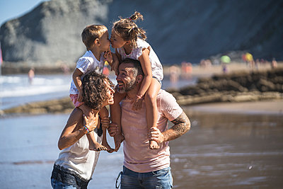 Sibling kissing while sitting on parents shoulder at beach - p300m2257254 by SERGIO NIEVAS