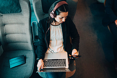 High angle view of businesswoman using various technologies while traveling in train - p426m1580136 by Maskot