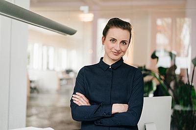 Junge Geschäftsfrau mit verschränkten Armen - p586m1451938 von Kniel Synnatzschke