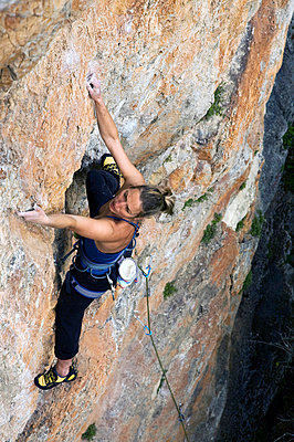 A climber makes her way up a steep and difficult route on the limestone cliffs in the Aveyron region, near Millau and Toulouse, south west France, Europe - p8713174 by David Pickford