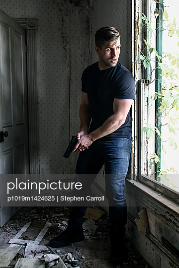 Armed man in hiding place - p1019m1424625 by Stephen Carroll