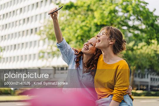 Two happy female friends taking a selfie in the city - p300m2140526 by Kniel Synnatzschke