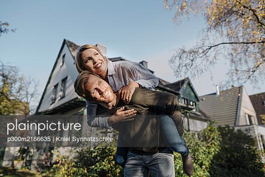 Man giving his wife a piggyback ride in garden - p300m2166635 von Kniel Synnatzschke