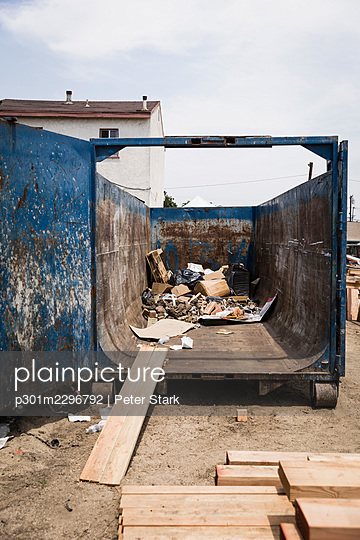 Wood plank leaning against dumpster with garbage - p301m2296792 by Peter Stark