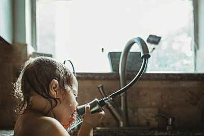 Close-up of girl playing with faucet while sitting against window in kitchen sink at home - p1166m1543900 by Cavan Images