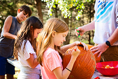 Three Young Children Carving Pumpkins Outdoors - p1166m2147178 by Cavan Images
