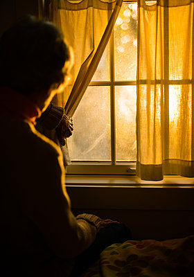 Elderly woman looking out of window - p1614m2211834 by James Godman