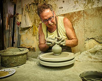 Potter in workshop working on earthenware vessel - p300m1191986 by Dirk Kittelberger