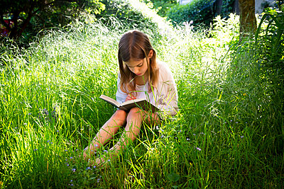Little girl sitting on a meadow reading a book - p300m2114713 by Larissa Veronesi
