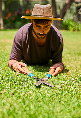 Man pruning the lawn in garden - p300m2156749 by Veam