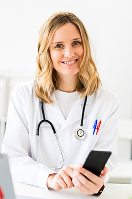 Smiling blond female doctor with smart phone sitting at desk - p300m2265389 by Giorgio Fochesato