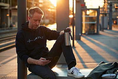 Man using cell phone at train station - p312m2207766 by Johan Alp