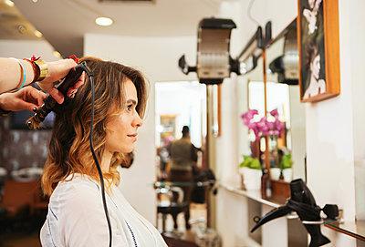 Hairdresser using curling tongs on customer's long brown hair in salon - p429m1408173 by Nancy Honey