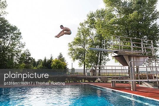 Mann springt vom Sprungturm in einem Schwimmbad, Leipzig, Sachsen, Deutschland - p1316m1160917 von Thomas Roetting
