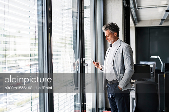 Mature businessman standing at the window in office holding cell phone - p300m1536162 by HalfPoint