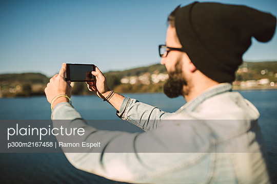 Young man taking smartphone selfies by the sea - p300m2167458 by Ramon Espelt