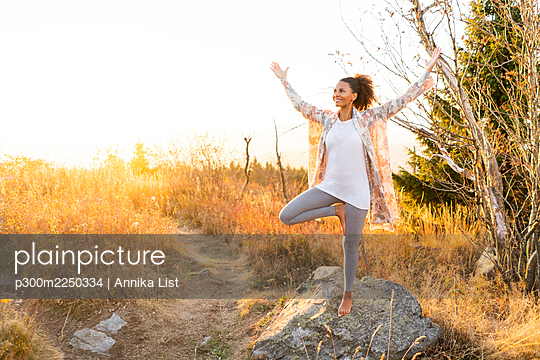 Woman practicing yoga while standing on rock during sunset - p300m2250334 by Annika List