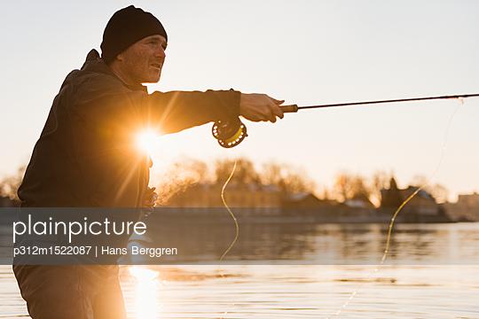 plainpicture | Photo library for authentic images - plainpicture p312m1522087 - Man fishing at sunset - plainpicture/Johner/Hans Berggren