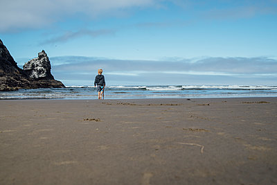Full length of boy holding stick while walking on sand at beach against sky - p1166m1524549 by Cavan Images