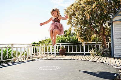 Little girl jumping on trampoline - p1640m2244885 by Holly & John