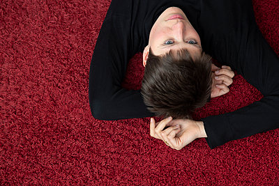 Young woman lying on a red carpet - p1650m2272223 by Hanna Sachau