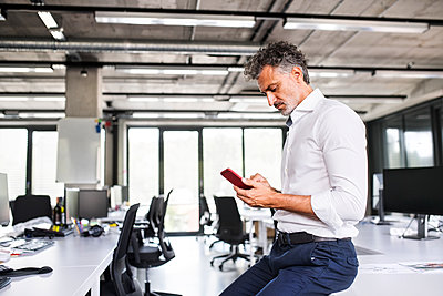 Mature businessman using cell phone in office - p300m1535266 by HalfPoint