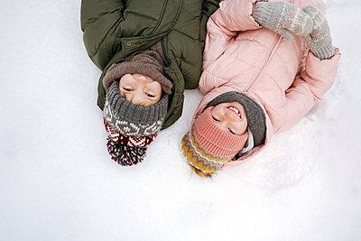 Portrait of two smiling siblings lying on snow - p300m2160462 by Ekaterina Yakunina