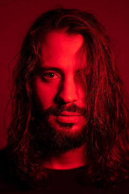 Portrait of red illuminated young man  against red background - p300m2188472 by Ezequiel Giménez
