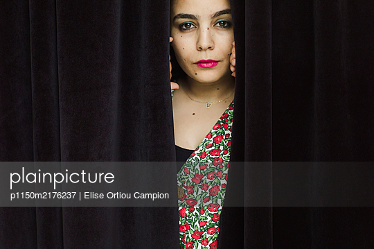 Woman peering through curtain - p1150m2176237 by Elise Ortiou Campion
