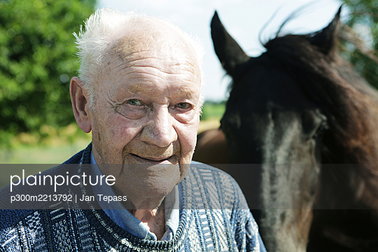 Germany, Portrait of senior man with horse, close up - p300m2213792 by Jan Tepass
