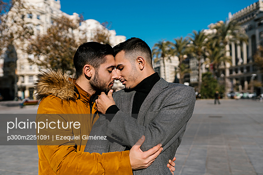 Gay men wearing jacket standing face to face with eyes closed in city - p300m2251091 by Ezequiel Giménez