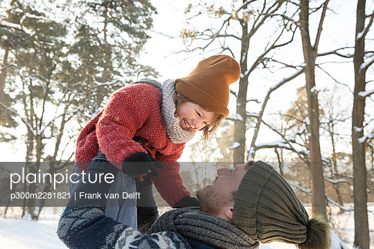 The Netherlands, Vught, father and sons playing in snowy woods - p300m2281821 von Frank van Delft
