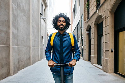 Portrait of smiling young man with backpack on E-Scooter after work, Barcelona, Spain - p300m2114510 von Josep Rovirosa