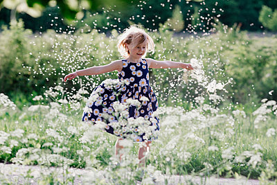 Portrait of smiling little girl playing with seeds of blowball - p300m2114807 von Oxana Guryanova