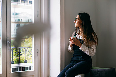 Thoughtful businesswoman looking through window while having coffee at office - p300m2188018 by Andrés Benitez
