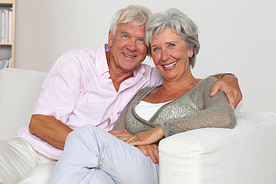 Senior couple hugging on sofa - p4737170f by Stock4B