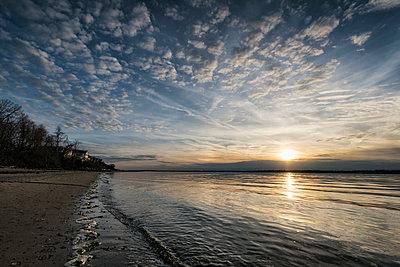 Sunset on ocean beach - p555m1232005 by Patrick Lienin