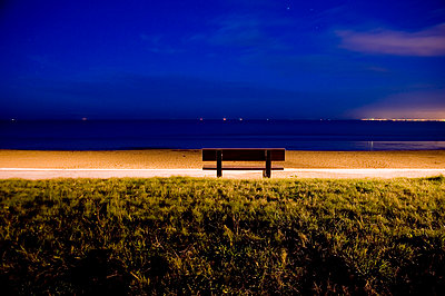 A solitary bench at dusk facing the sea - p589m1185277 by Thierry Beauvir