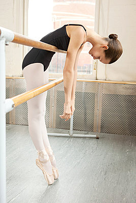 Ballerina leaning over barre - p9245500f by Image Source