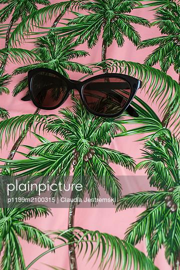 Sunglasses on a palm tree patterned tablecloth - p1199m2100315 by Claudia Jestremski