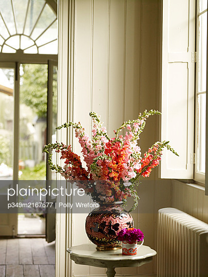 Flowers on side table in entrance hall - p349m2167677 by Polly Wreford