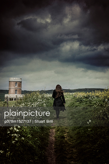 Woman on path by tower - p378m1527137 by Stuart Brill