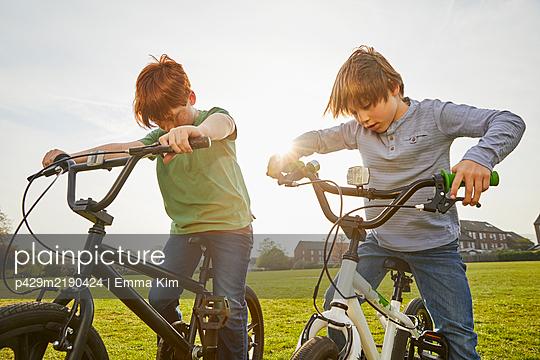 Two boys riding their BMX bikes in a park. - p429m2190424 by Emma Kim