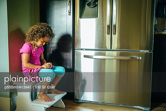 Sad mixed race girl sitting near refrigerator
