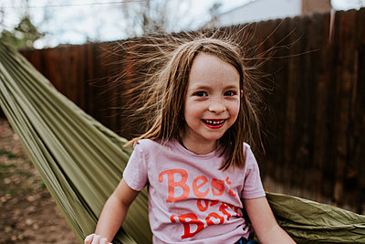 Young girl with static hair sitting on hammock - p1166m2201354 by Cavan Images