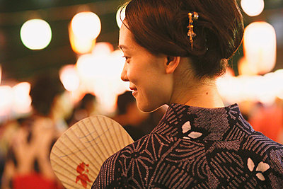 Young Japanese woman in a traditional kimono at a summer festival - p307m935867f by Yosuke Tanaka
