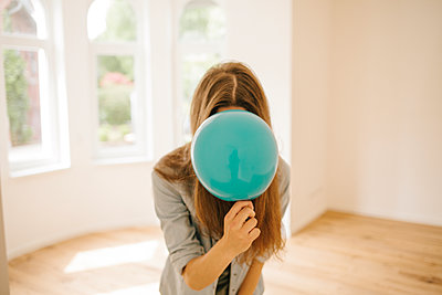 Young woman in new apartment playing with balloon - p586m1064880 by Kniel Synnatzschke