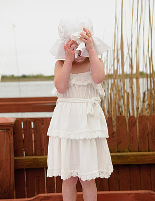 Girl covering face with white sunhat - p924m711063f by Matt Dutile