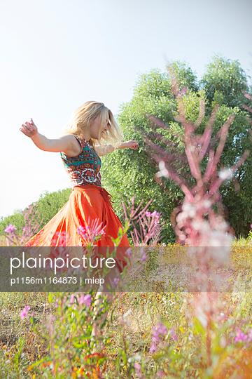 Junge Frau tanzt durch Sommerwiese - p1156m1164873 von miep