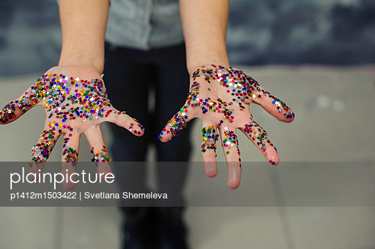 The girl demonstrates with open palms strewn with confetti in the shape of stars - p1412m1503422 by Svetlana Shemeleva